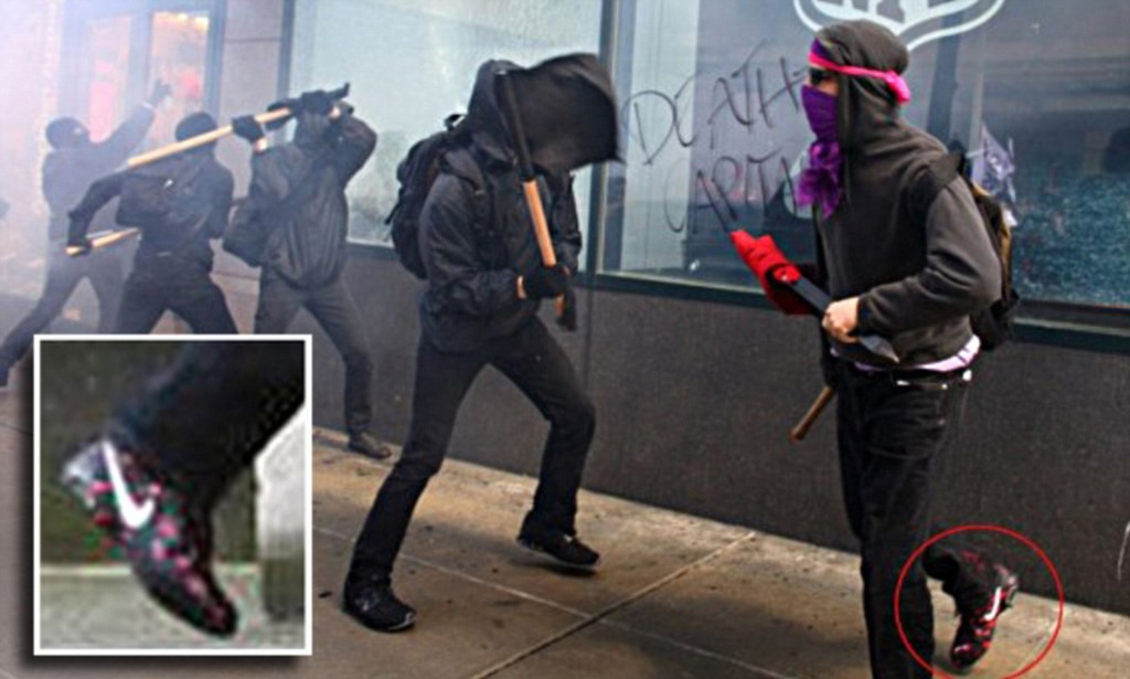 What not to wear as an anarchist. This protester was trying to break a Bank of America window in downtown Seattle during the May Day protests on May 1, 2012. Link to Seattlepi: http://blog.seattlepi.com/thebigblog/2012/05/02/the-seattle-anarchist-who-wore-the-wrong-outfit/anarchist-nike/