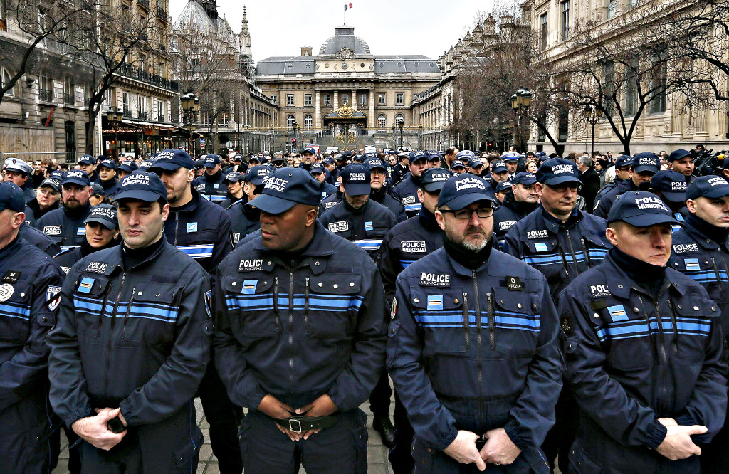 French municipal Police officers react as they attend a national tribute for the three officers killed during last week's terrorist attacks, in front of Paris Prefecture...French municipal Police officers react as they attend a national tribute for the three officers killed during last week's terrorist attacks, in front of Paris Prefecture, January 13, 2015. The three police officers were killed in terror attacks at the offices of satirical weekly Charlie Hebdo and in the streets of Montrouge, outside the French capital. REUTERS/Gonzalo Fuentes (FRANCE - Tags: POLITICS CRIME LAW)
