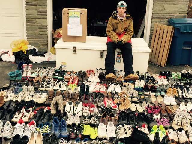 Joshua Zeiser sits in front of the shoe collection he amassed for Soles4Souls before packing the donations into boxes to be shipped. Photo provided.